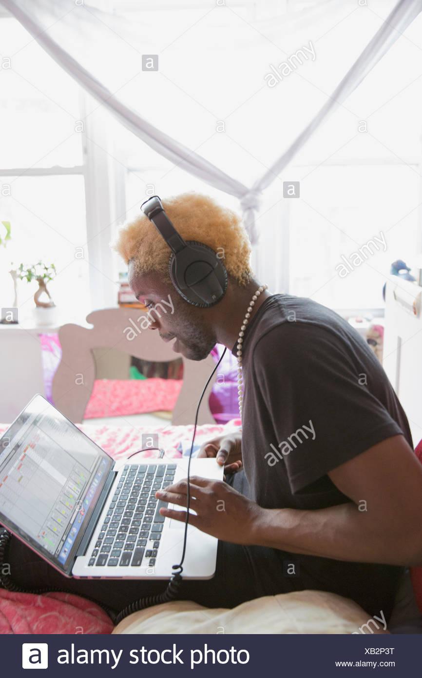 Junger Mann mit der Eingabe auf seinem Laptop mit Kopfhörern Stockbild