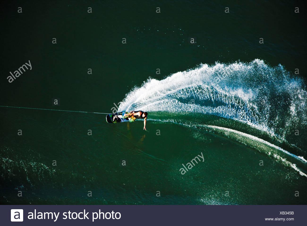 Eine sportliche Wakeboarder schnitzt und Schrägstriche an einem ruhigen Tag in Idaho. Erschossen von oben. Stockfoto