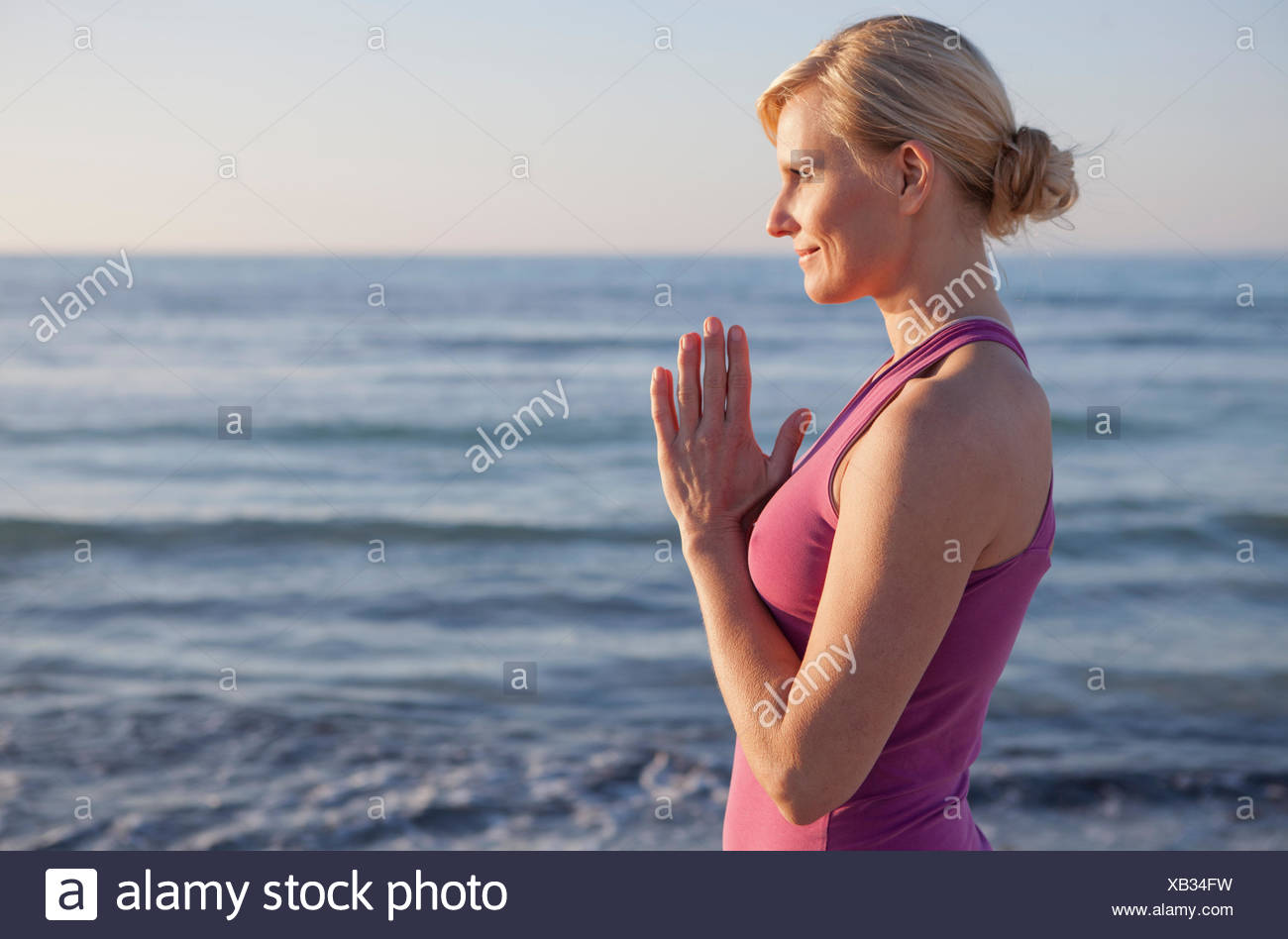 Frau in Yoga-Gebet-Pose am Strand Stockbild