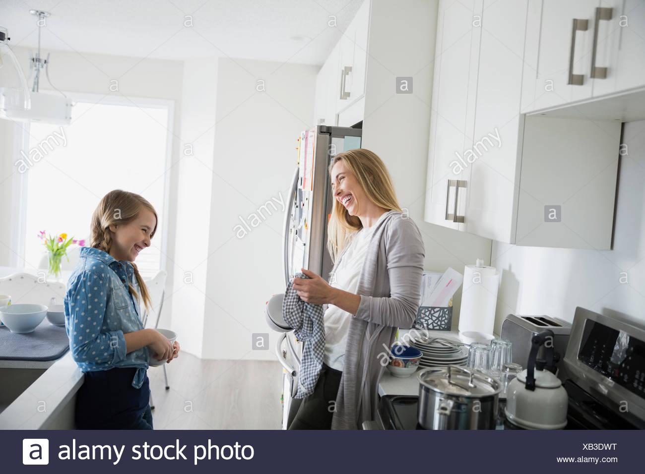 Mutter und Tochter lacht und Trocknung Gerichte Stockbild