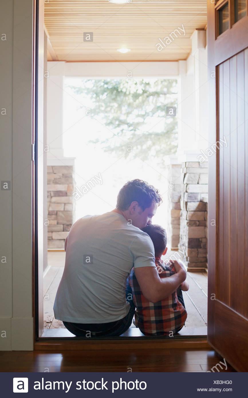 Vater und Sohn sitzen in Tür Stockbild