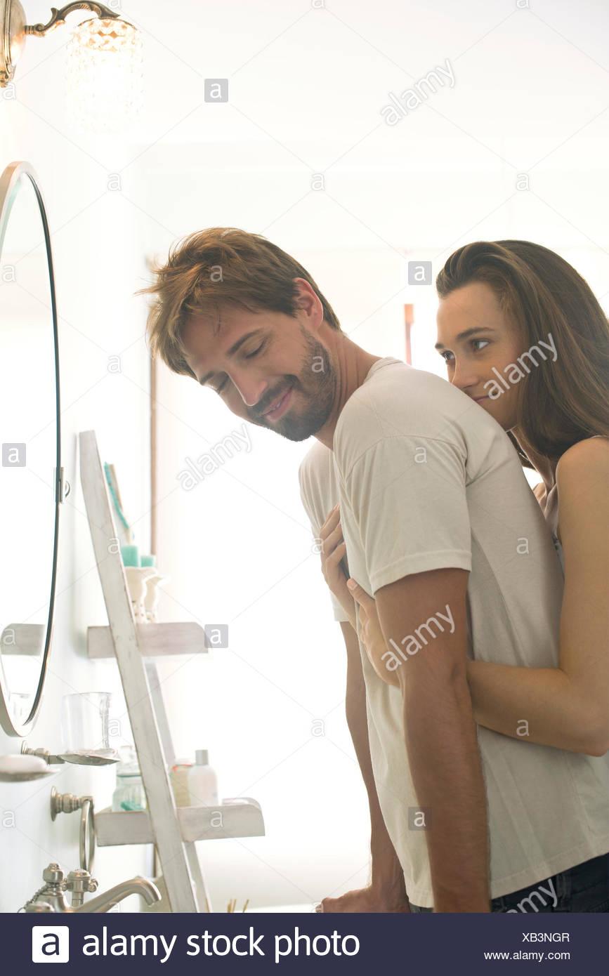 Frau umarmen Freund von hinten Stockbild