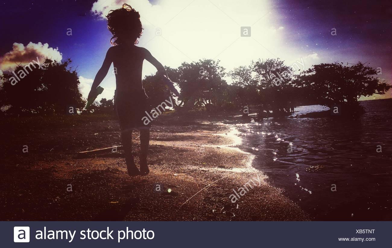 Silhouette der junge am Strand springen Stockbild