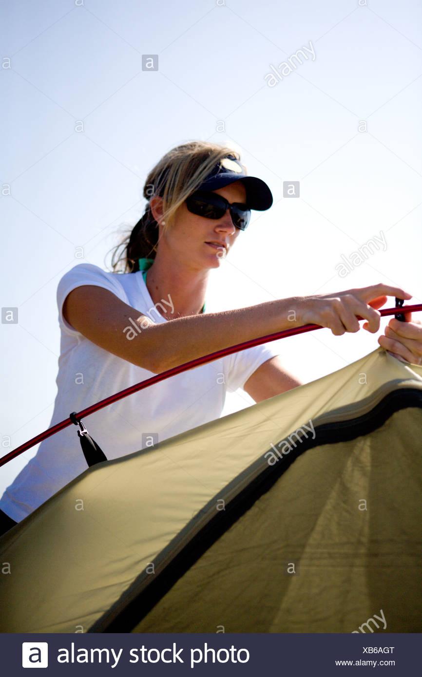 Eine blonde Frau mit Sonnenbrille stellt ein Zelt in der Sonne. Stockbild