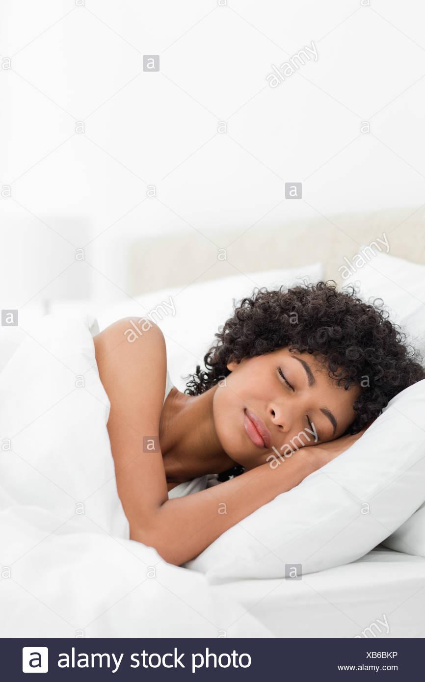 Krauses dunkelhaarige Frau friedlich schlafend Stockbild