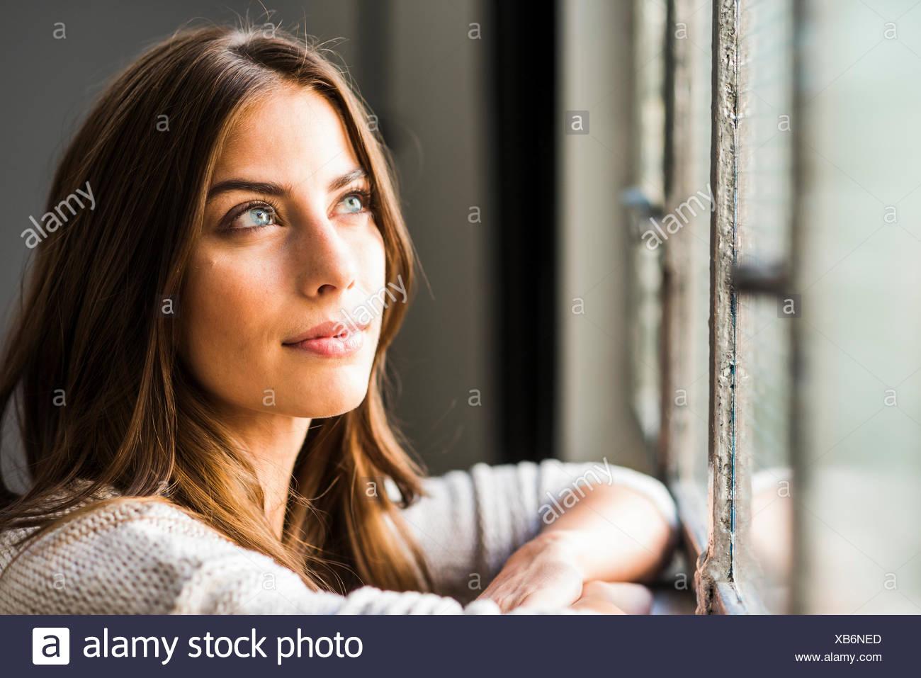 Brünette Frau aus Fenster Stockbild