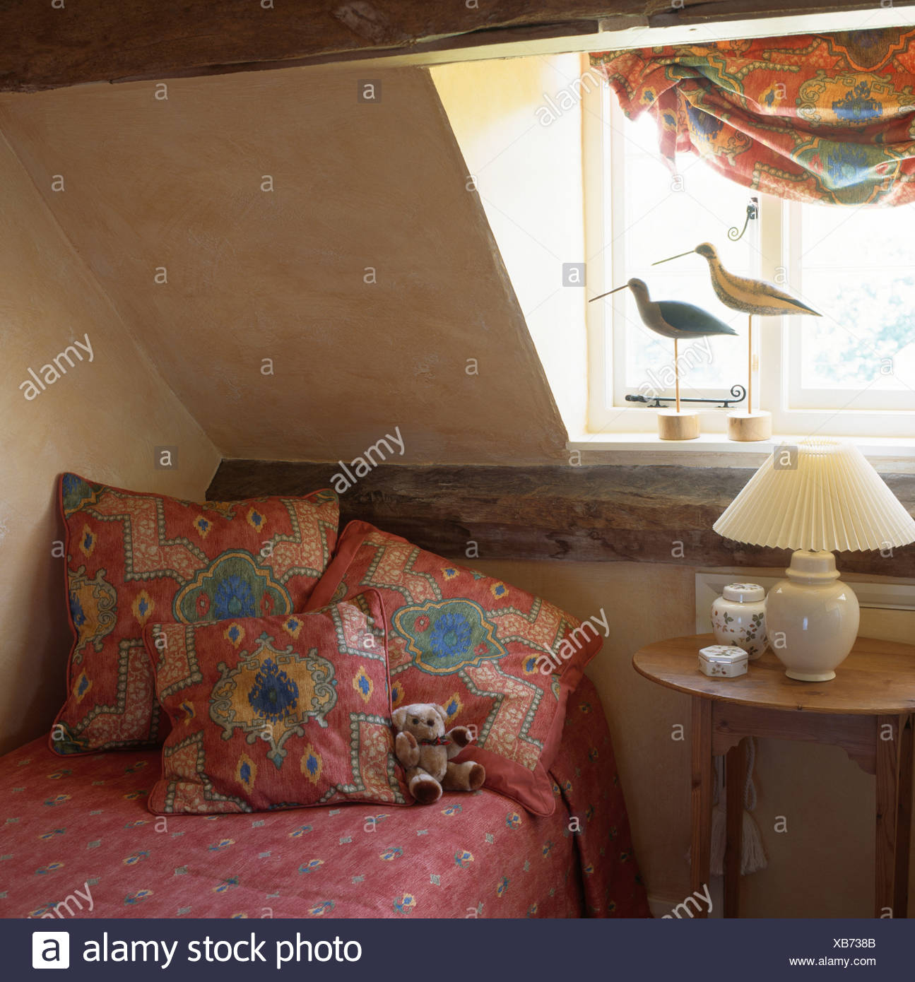 Gemusterte rote Kissen auf Bett unter Fenster im ...
