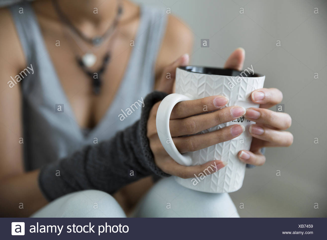 Junge Frau trinkt Kaffee Pulswärmer hautnah Stockbild
