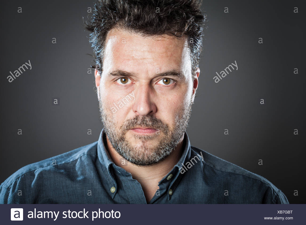 Porträt von ernster Mann stehend vor grauem Hintergrund Stockfoto