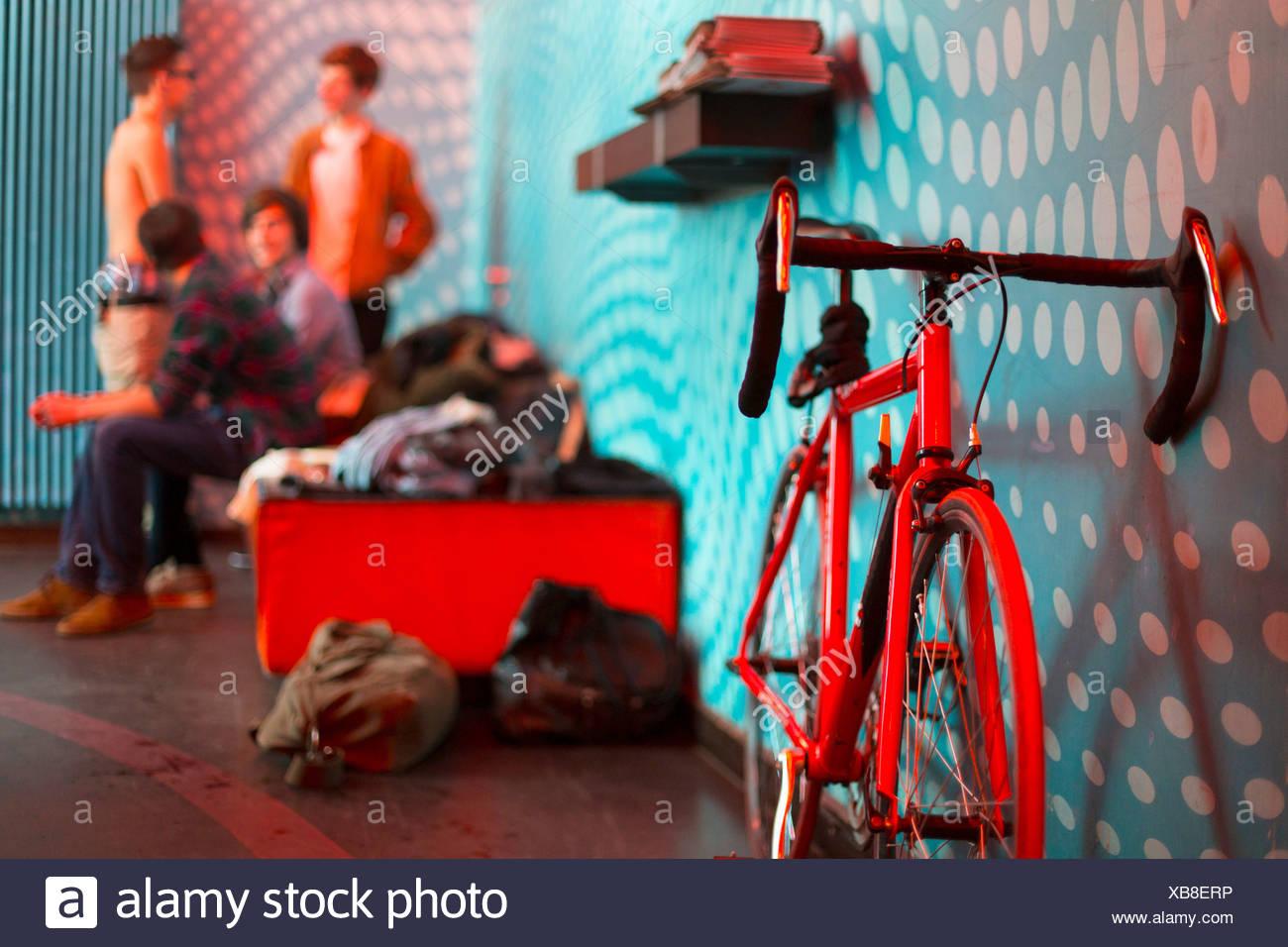 Fahrrad im Vordergrund, Gruppe von vier jungen im Teenageralter im Hintergrund Stockbild
