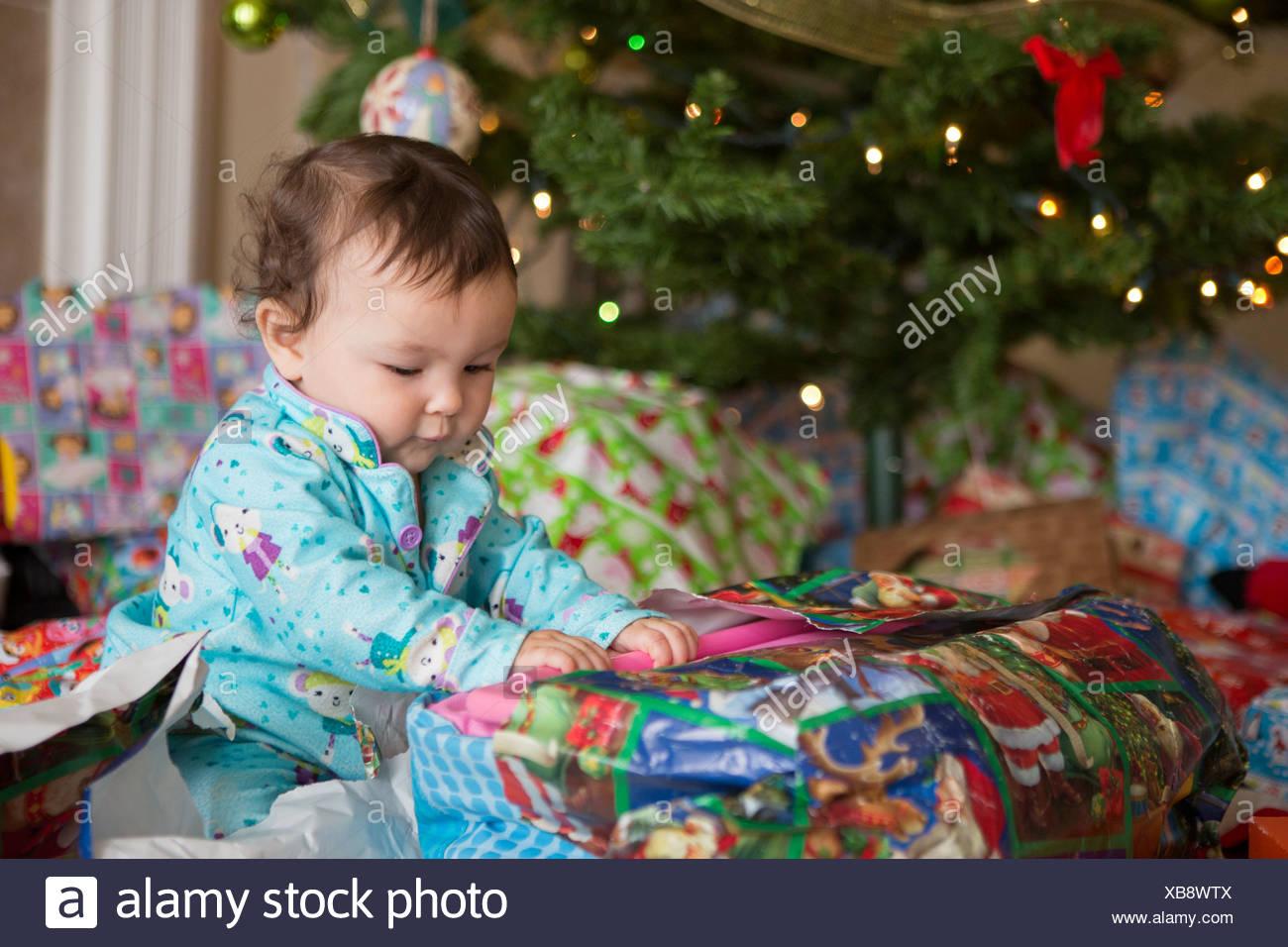Babymädchen Eröffnung präsentiert ihr erstes Weihnachten Stockbild