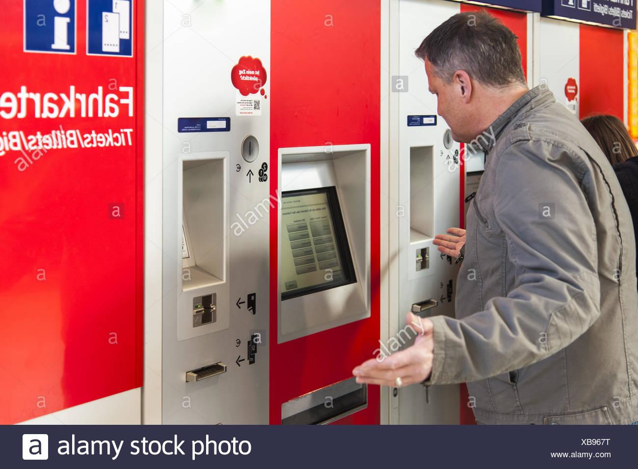 ein Mann steht vor einem verzweifelten Ticket machin Stockbild