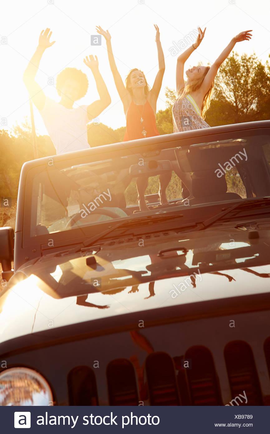 Drei Frauen tanzen auf der Rückseite Open Top Car Stockbild