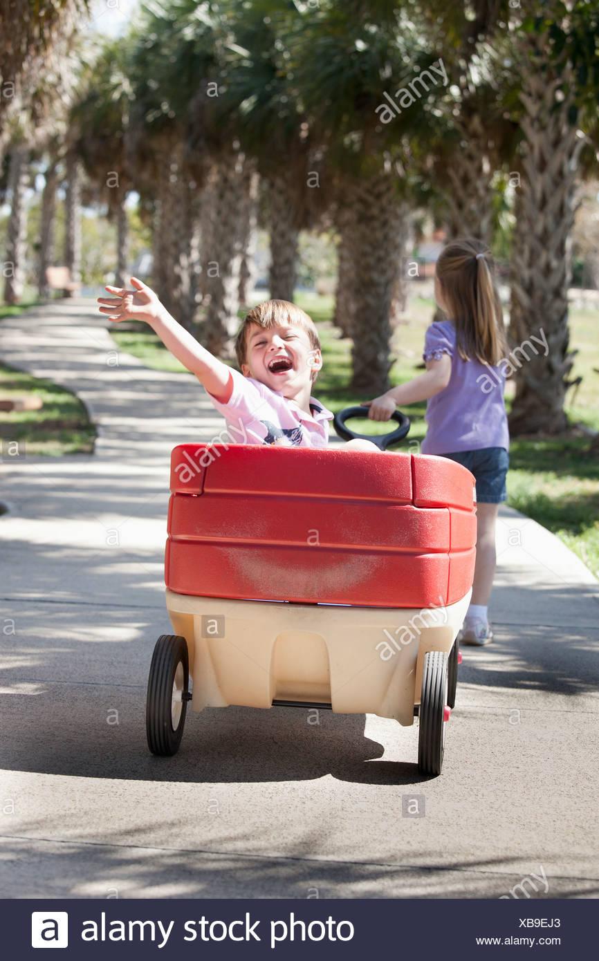 Ein Mädchen einen Wagen ziehen, während ein Junge im Rahmen sitzt ...