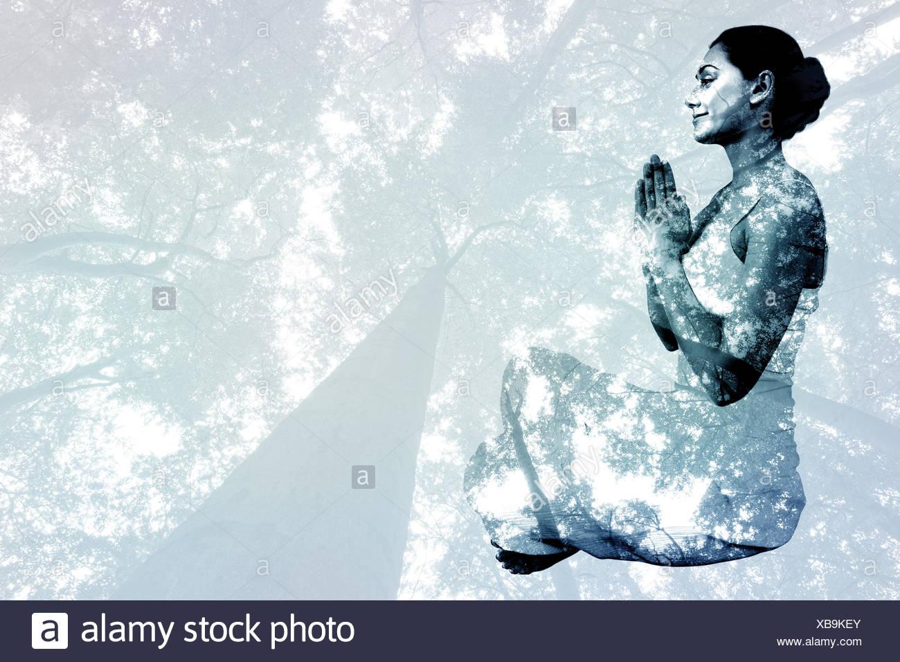 Zusammengesetztes Bild Inhalt Brünette in weißen sitzen in Lotus-pose Stockbild