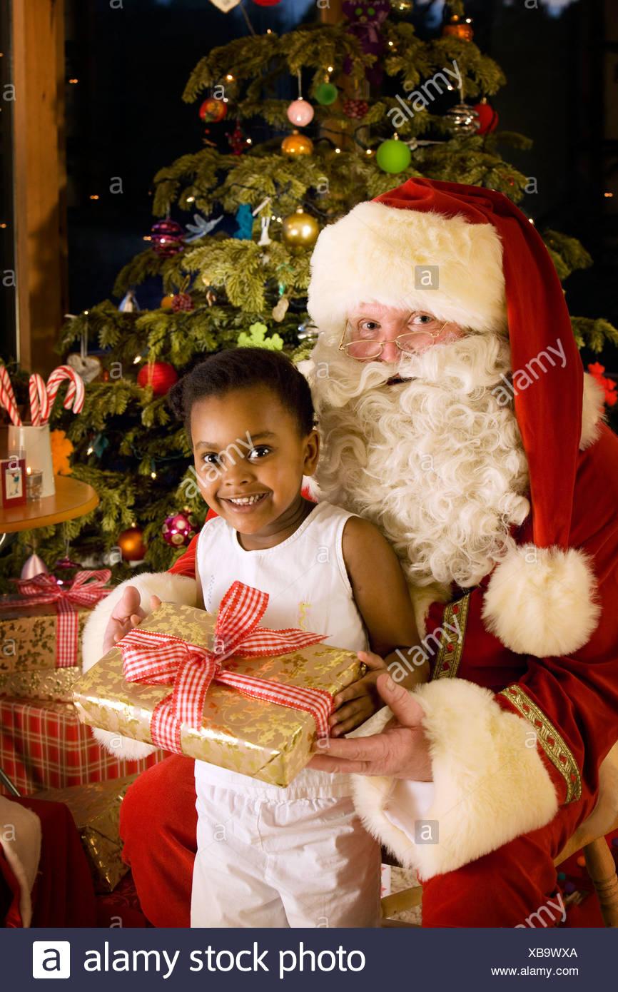 Weihnachtsmann und Mädchen hält Weihnachtsgeschenk Stockfoto, Bild ...