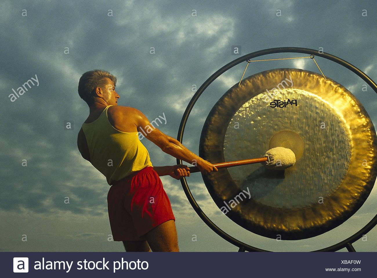 Mann, Gong, Hit, Signal, Ton, Kultur, Tradition, in Chinesisch, asiatisch, Hammer, Schlag, groß, rund, Messing, Bronze, Stockbild