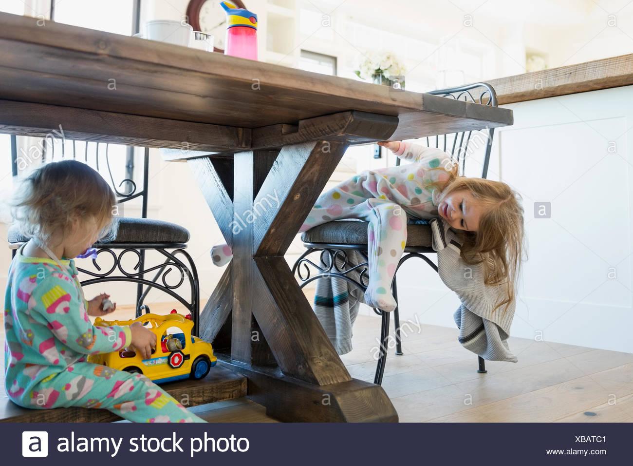 Mädchen im Schlafanzug spielen unter Esstisch Stockfoto