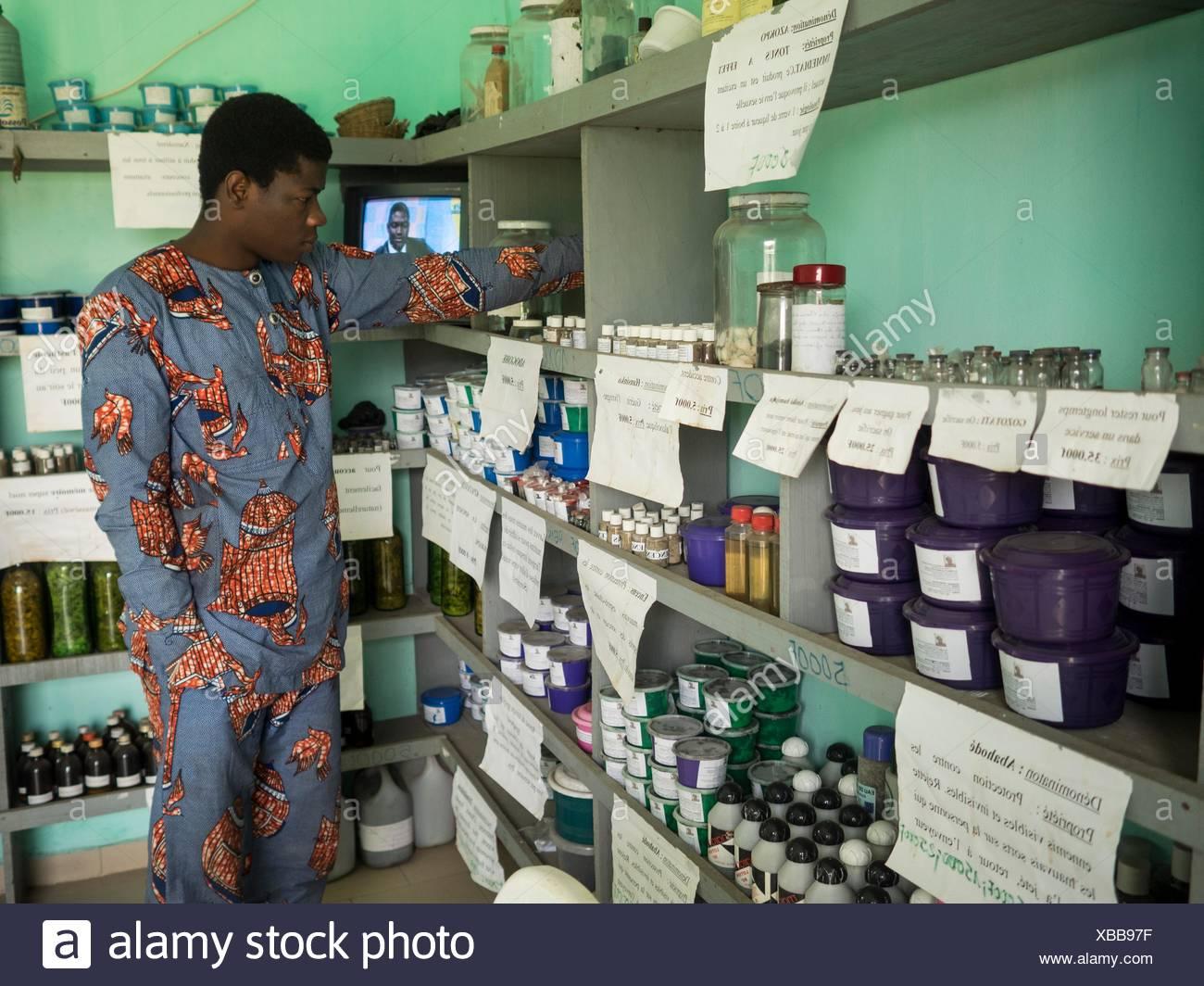Ein Mann untersucht Flaschen traditioneller Arzneimittel verschrieben für eine Vielzahl von Beschwerden, wie zum Beispiel Stress, Infektion, als Erinnerungshilfen und Exorzismus. Stockbild