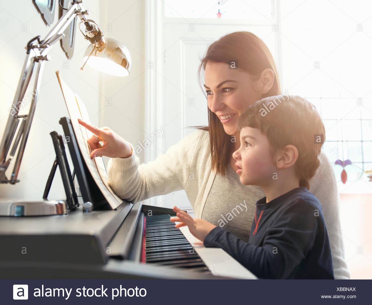 Mutter zeigt auf Noten Sohn zu Hause Klavier spielen beibringen Stockbild