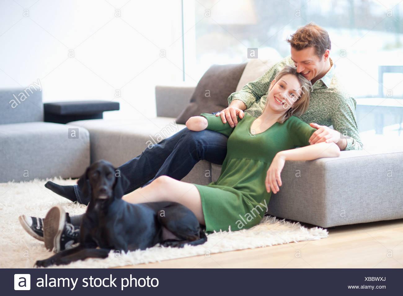 Junges Paar sitzt im Wohnzimmer mit Hund, Frau mit amputierten arm Stockbild
