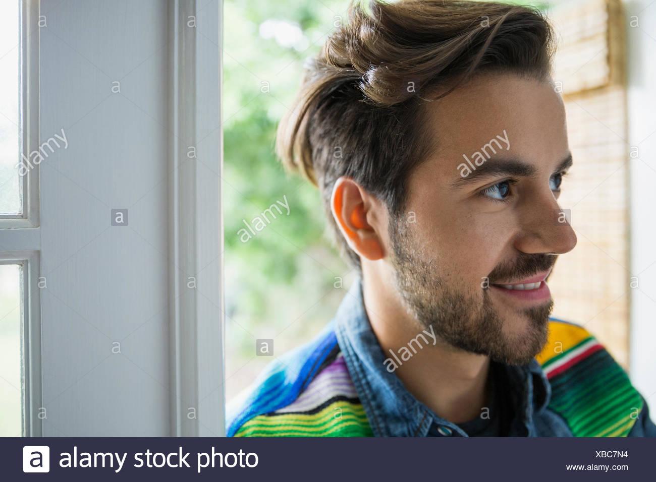 Lächelnde Brünette Mann in der Tür wegschauen Stockbild