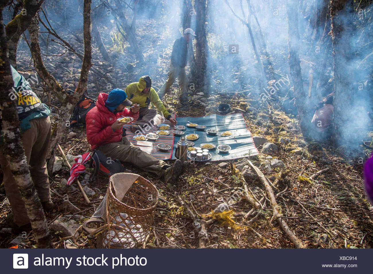 Zwei Expeditionsteilnehmer Essen essen, während die anderen sich um den Campingplatz beschäftigt. Stockbild