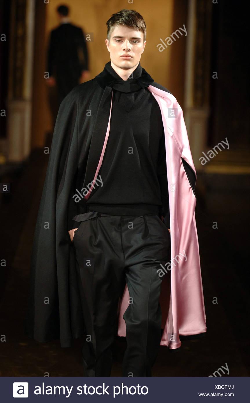 Blonde Männermodel trägt einen schwarzen Pullover, Hosen und