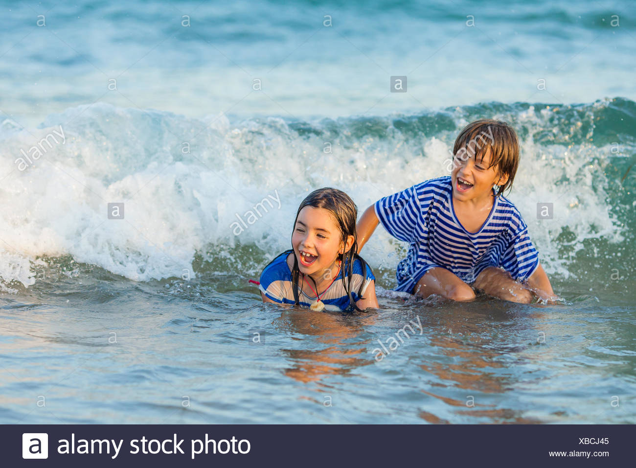 Zwei Kinder spielen im Meer Stockbild