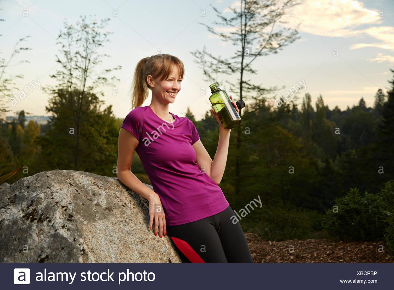 Weibliche Läufer gelehnt Boulder im Park Trinkwasser Stockbild