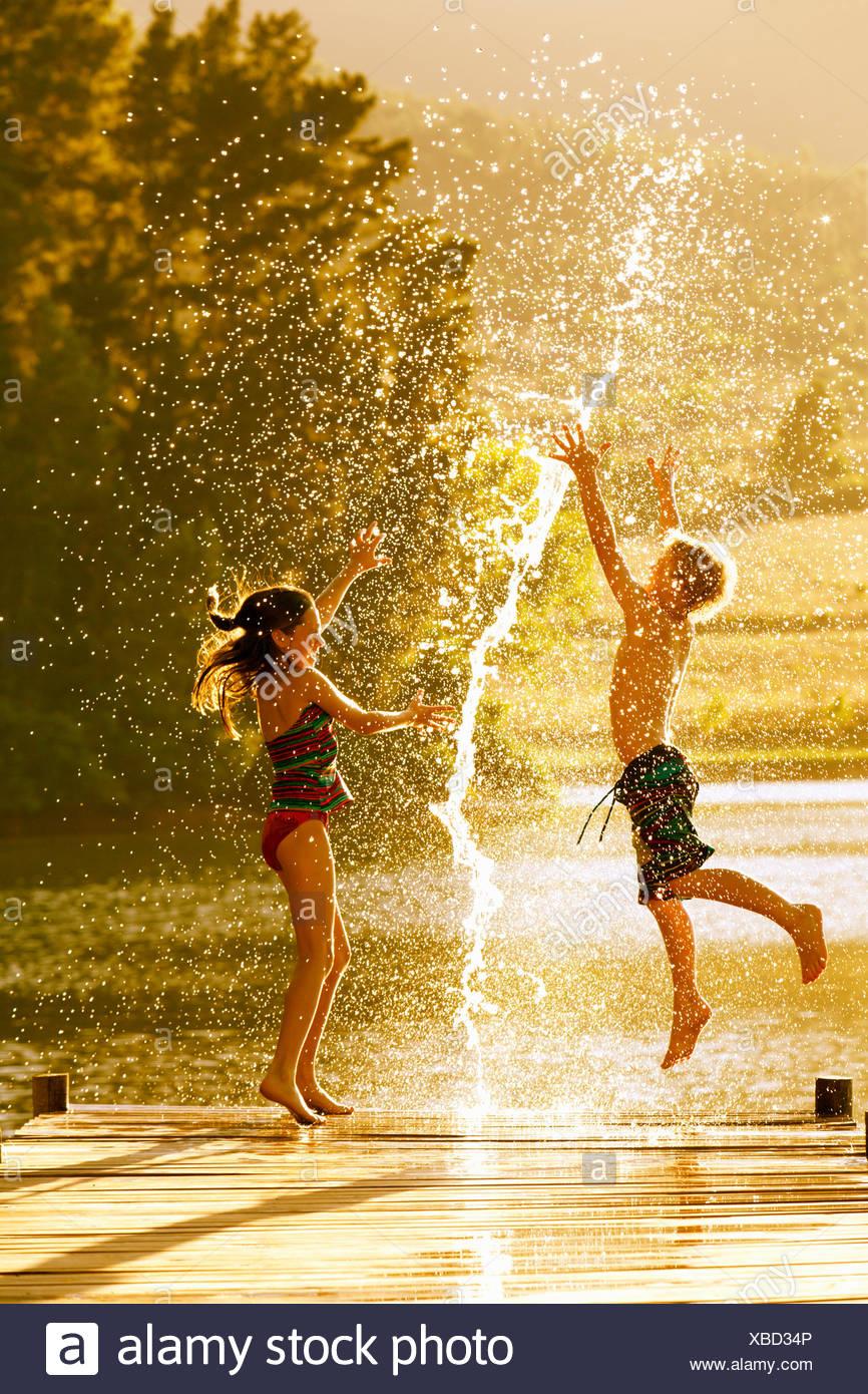 Jungen und Mädchen in Luft auf Steg durch Spritzer Wasser springen Stockbild