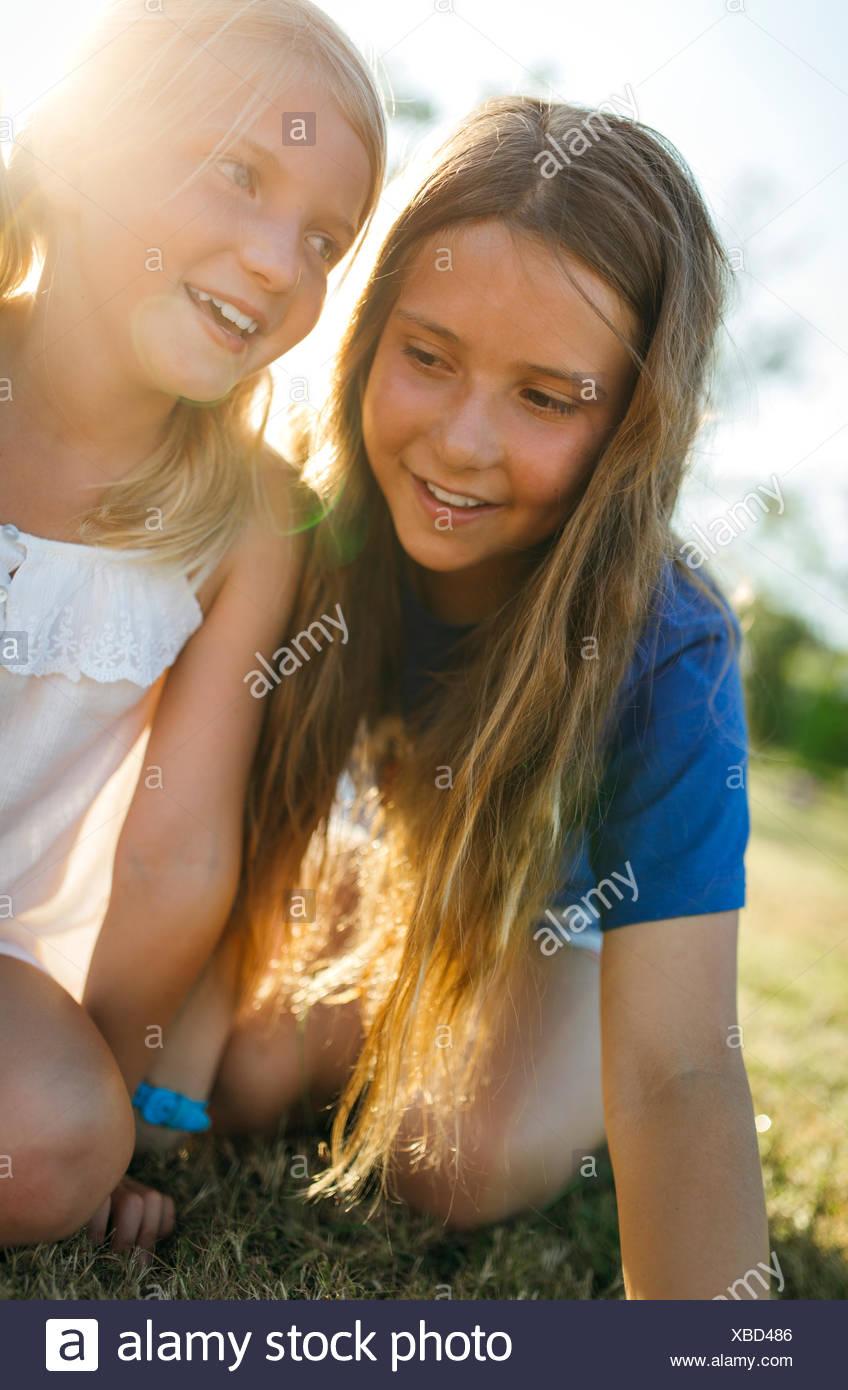 Zwei Schwestern, die nebeneinander auf einer Wiese hocken Stockbild