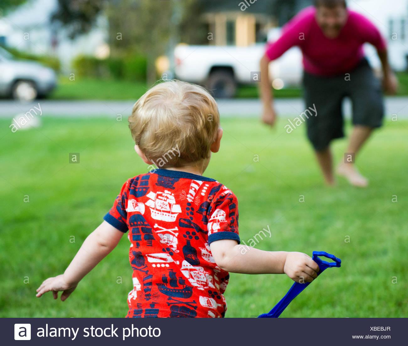 Vater und Sohn spielen im Garten Stockbild
