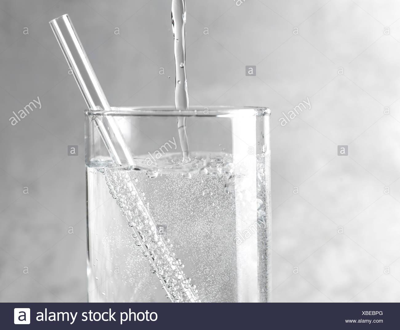Detail der funkelnden Wasser in ein Glas mit einer durchsichtigen Strohhalm auf grauem Hintergrund aus Metall gegossen wird. Stockbild
