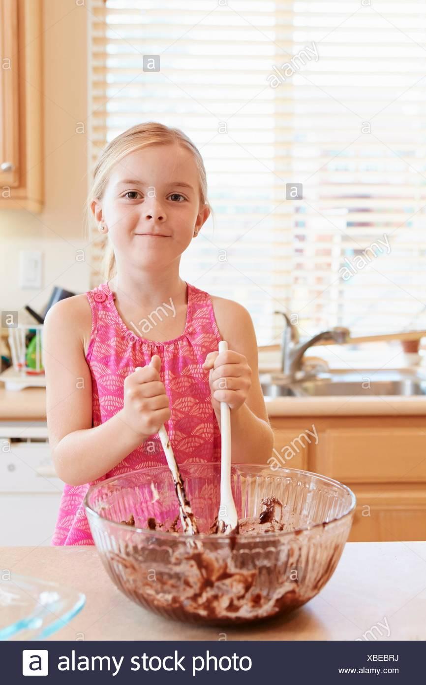 Mädchen, die Schmelzen der Schokolade in eine Rührschüssel geben Stockbild
