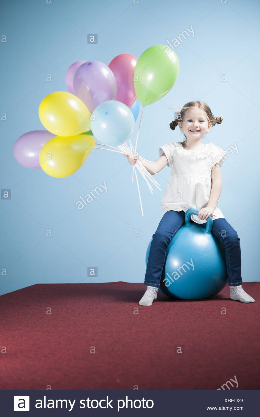 Junges Mädchen hält Luftballons auf ein Hoppity Pferd Stockbild