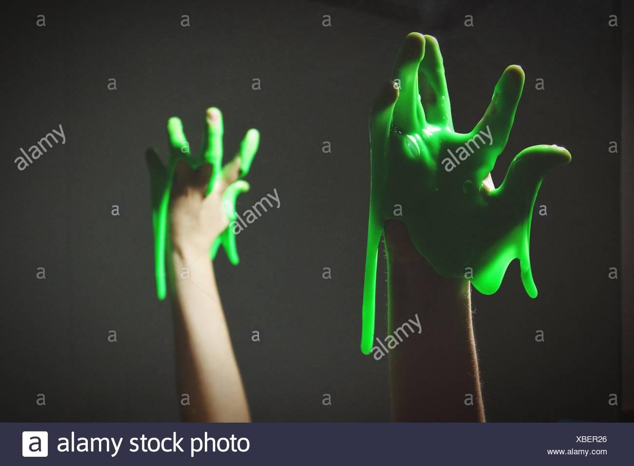 Abgeschnitten von Hand mit grünen Schleim auf schwarzem Hintergrund Stockbild