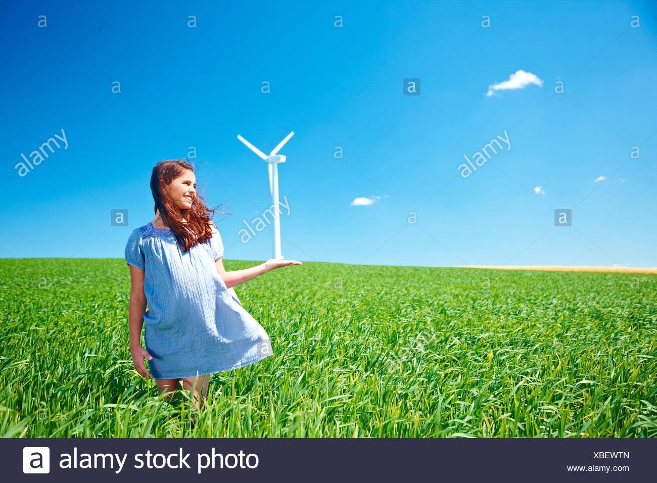 Mädchen mit Windturbine auf Feld Stockbild
