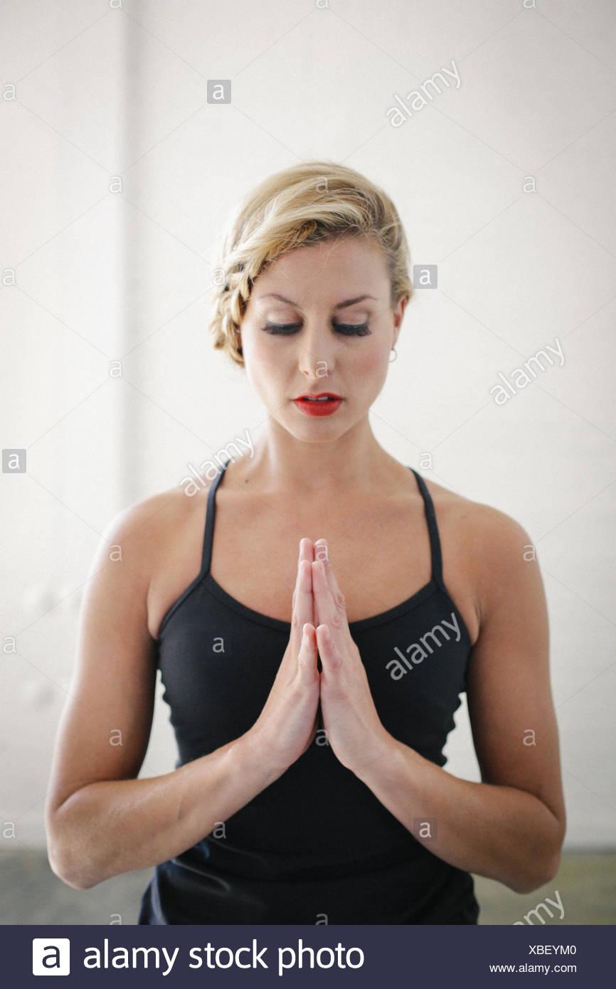 Eine blonde Frau in eine schwarze Trikot beim Yoga, stehen mit geschlossenen Augen und ihre Hände zusammen. Stockfoto