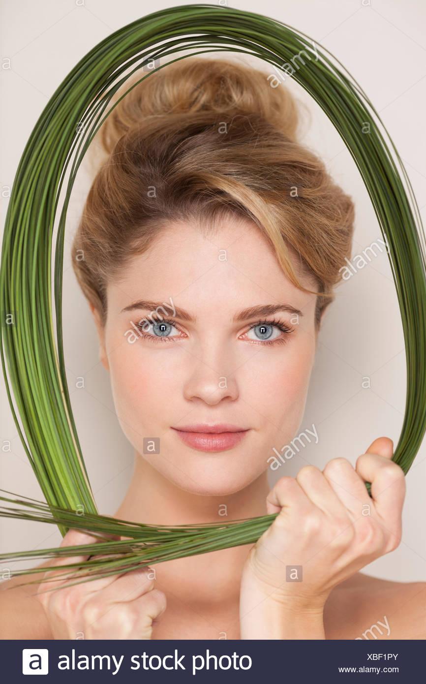 Porträt einer schönen Frau mit Weizengras Stockbild