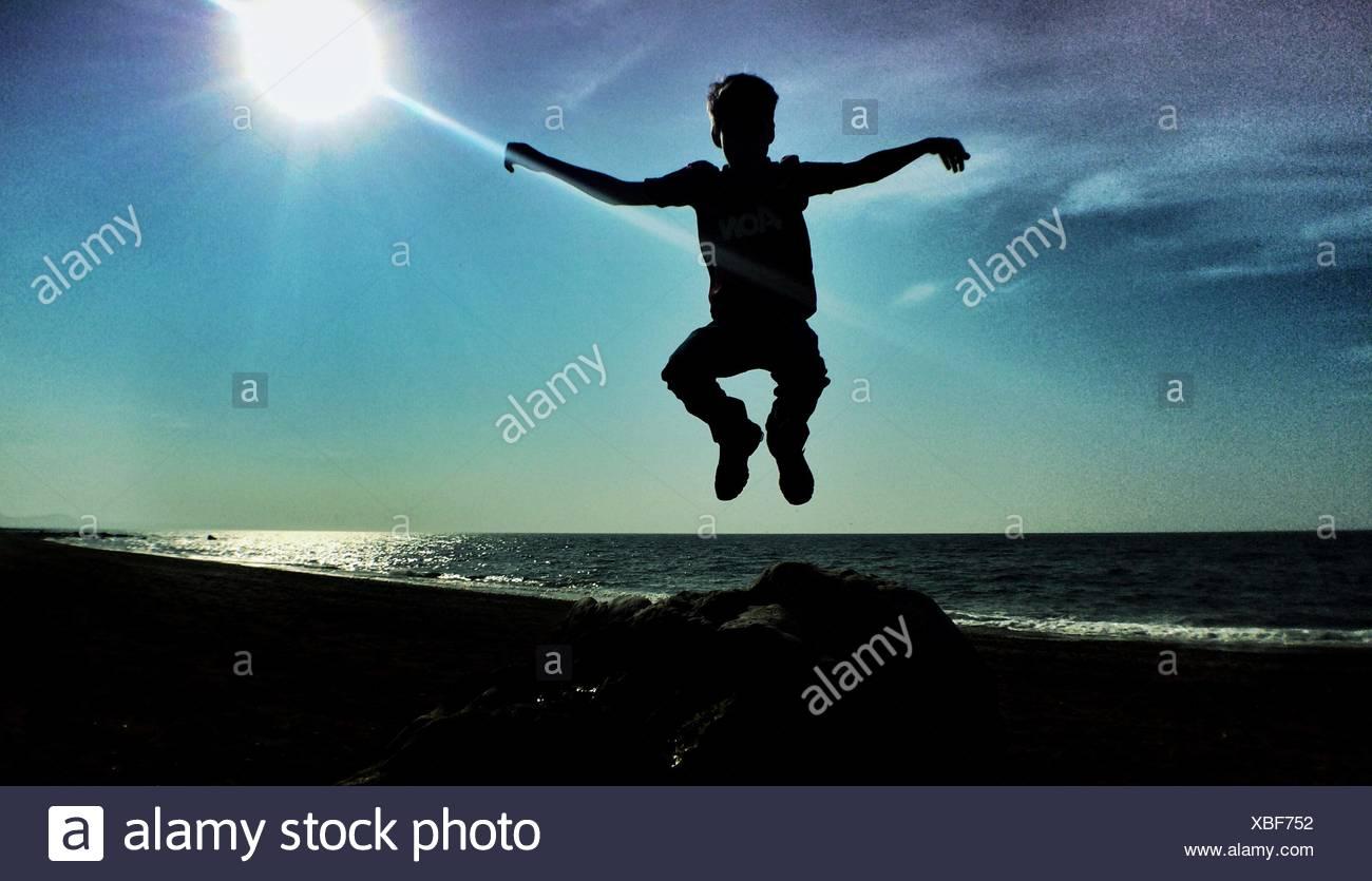 Junge springt in die Luft gegen Sonne Stockbild