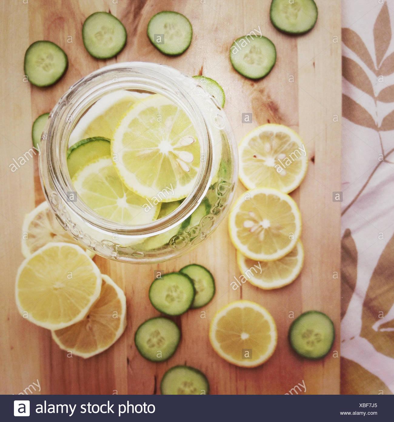 Blick von oben auf ein Glas mit Zitronen- und Gurkenscheiben gefüllt Stockfoto