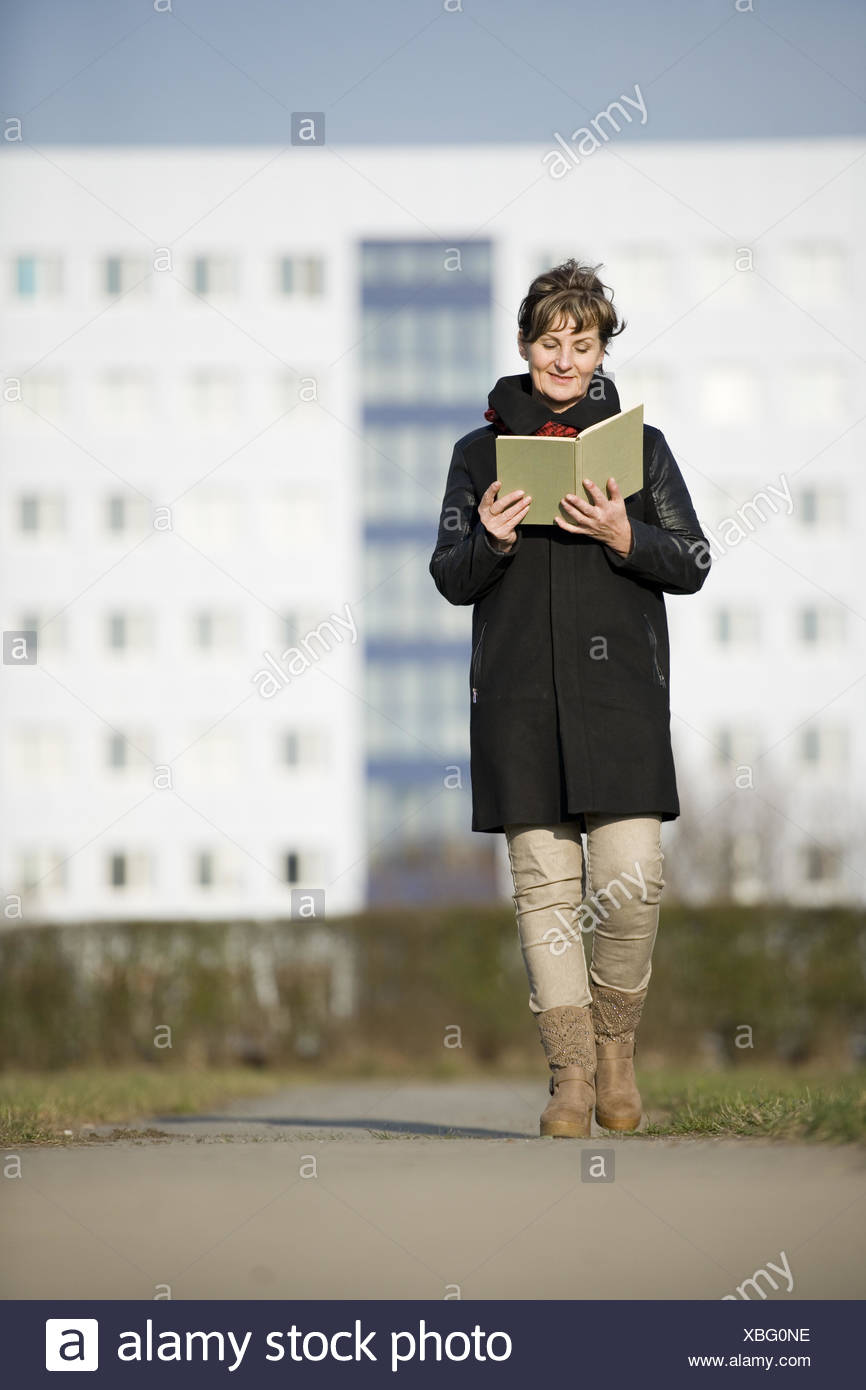 Frau zu Fuß und reading_near Stockbild