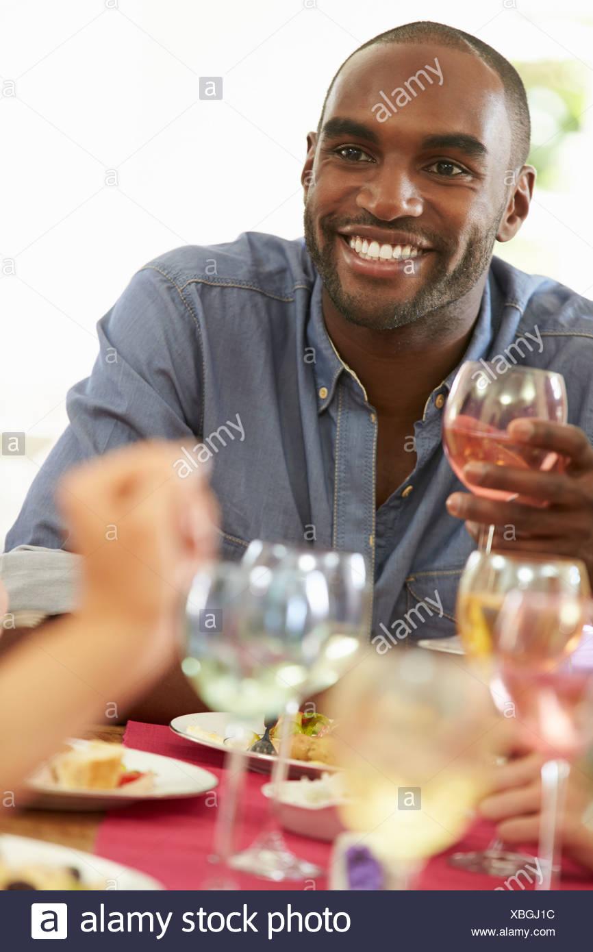 Junger Mann entspannen bei Dinner-Party Stockbild