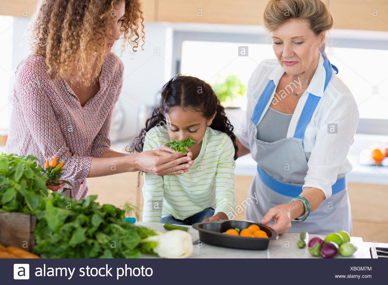 Ältere Frau mit Tochter und Enkelin in Küche Stockbild