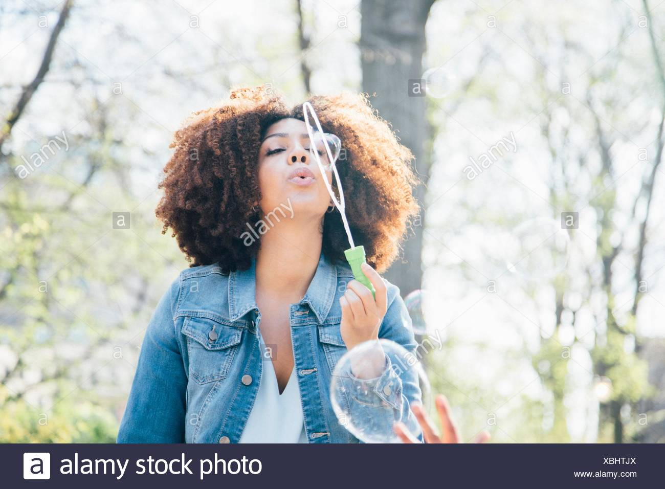 Vorderansicht der Mitte Erwachsene Frau bläst Seifenblasen, Augen geschlossen, nach oben Stockbild