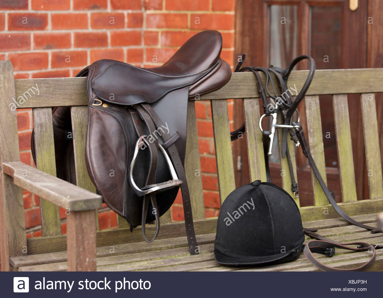 Pferdesattel, Zügel und Helm auf Bank Stockbild