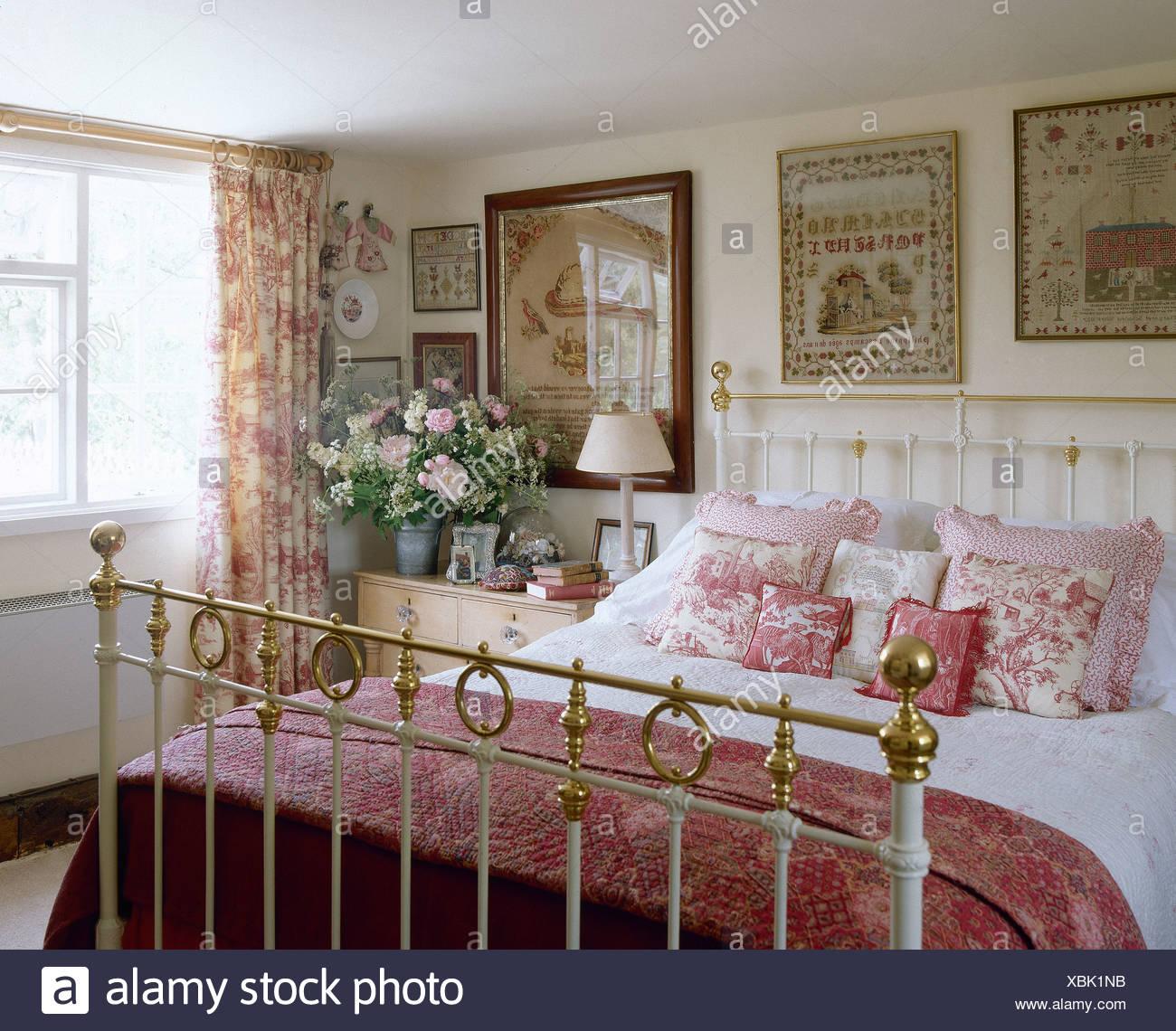 Antiken Sampler an Wand über antike Messingbett mit rosa Decke und ...