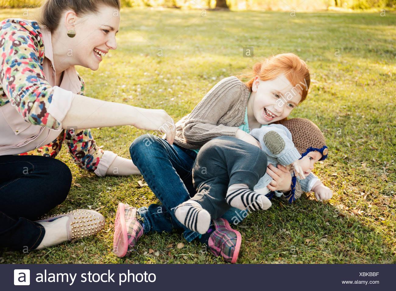 Mitte Erwachsene Mutter, Tochter und Baby Sohn auf dem Rasen im park Stockbild