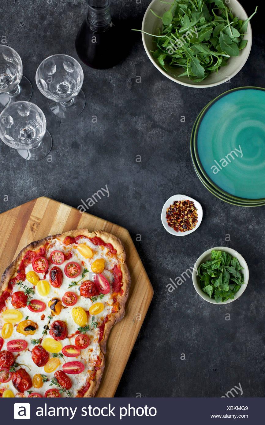 Geröstete Tomaten Pizza mit einer dünnen Olivenöl Crackerkruste.  Fotografiert auf schwarz/grau Hintergrund aus Draufsicht. Stockbild